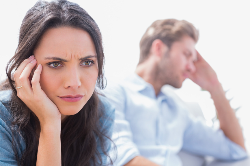 Stressed woman holding her head next to her partner