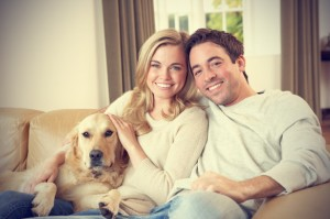 happy-couple-in-their-living-room-with-their-dog