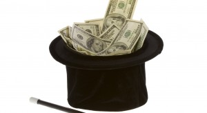 US Currency One Hundred Dollar Bills in a black magic hat with a magic wand, isolated on white background.